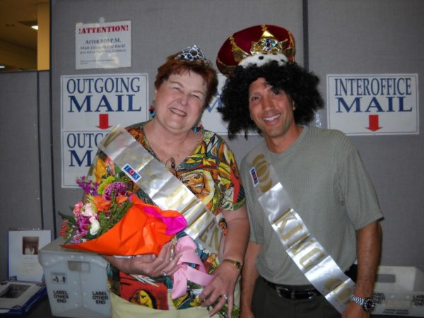 Employees wearing sashes and a crown