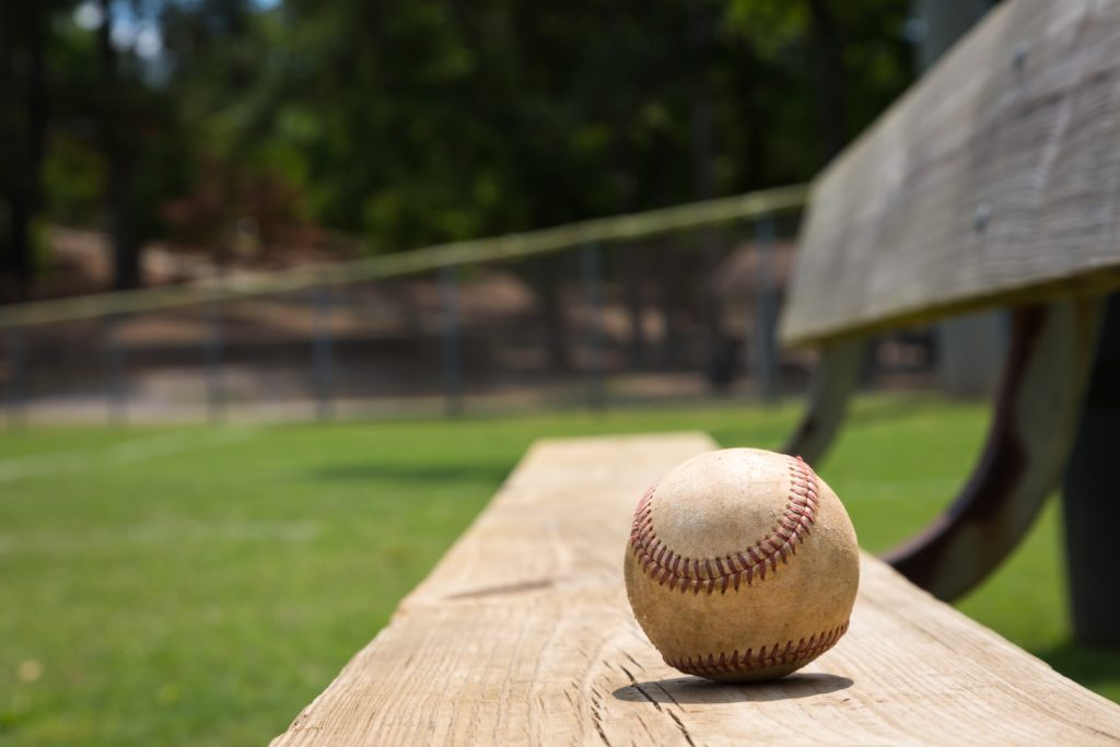 Single baseball on bench in a park.