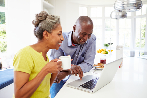 Couple looking at computer while drinking coffee