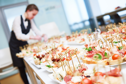 Female caterer preparing food for a large event.