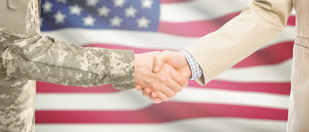 Shaking hands in front of American flag.